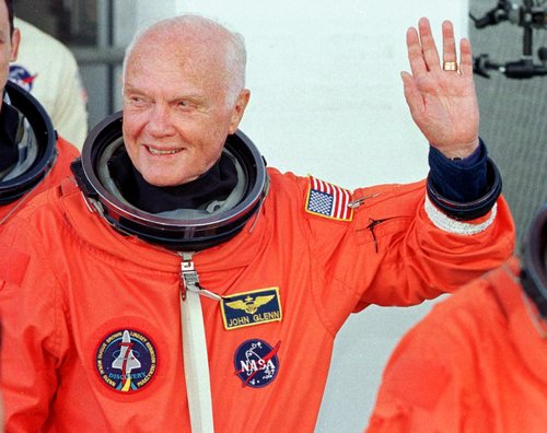 John Glenn waves as he leaves the operations and check out building at the Kennedy Space Center on October 29, 1998