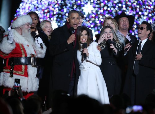 U.S. President Barack Obama sings 'Jingle Bells' with Eva Longoria, Marc Anthony, James Taylor, Trisha Yearwood, Garth Brooks, Kelly Clarkson, Caroline Smedvig, Sasha Obama and Santa Claus during the National Christmas Tree lighting ceremony, on December