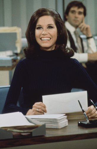 Mary Tyler Moore (as Mary Richards) smiles broadly as she sits at a desk in a scene from 'The Mary Tyler Moore Show' in Los Angeles circa 1970