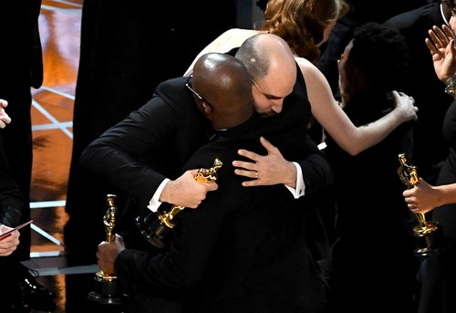 La La Land' producer Jordan Horowitz hands over the Best Picture award to 'Moonlight' writer/director Barry Jenkins following a presentation error onstage during the 89th Annual Academy Awards at Hollywood & Highland Center on February 26, 2017 in Hollywo