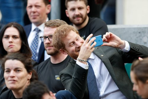 Prince Harry takes a photograph as he sits with competitors from the 2014 and 2016 Invictus Games in the crowd watching the annual Army Navy armed forces rugby match at Twickenham stadium on April 29, 2017 in London
