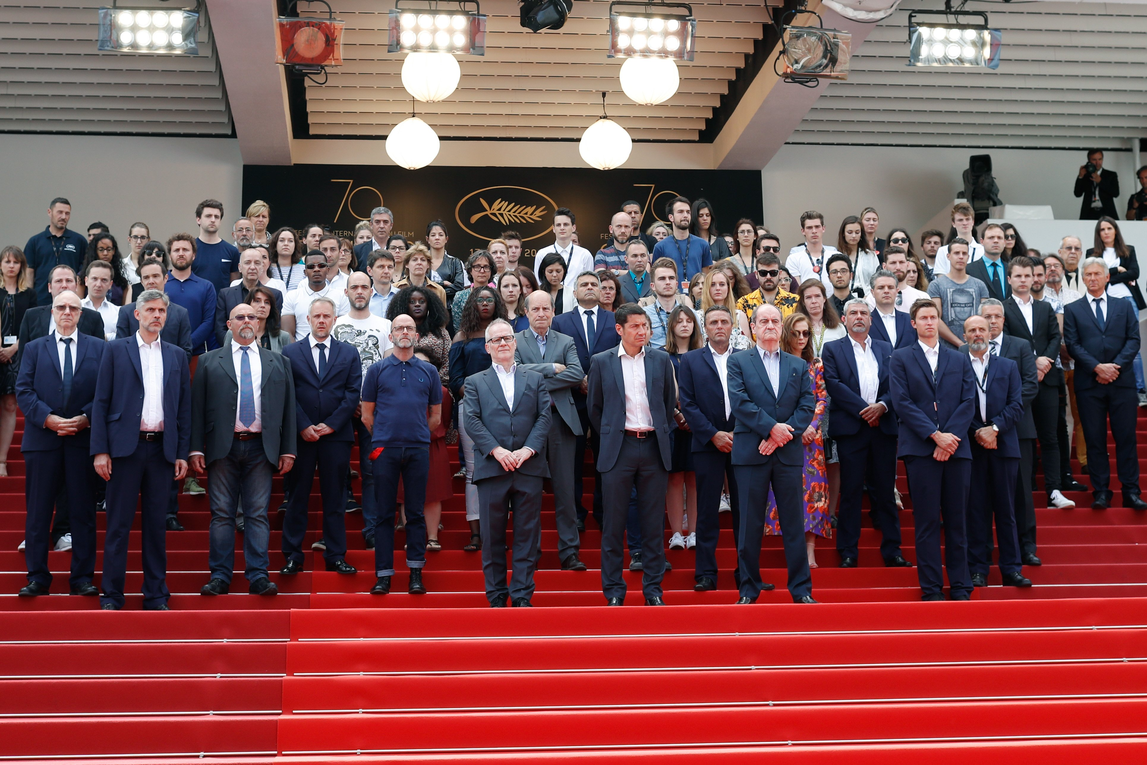 Director of the Cannes Film Festival Thierry Fremaux and President of the Cannes Film Festival Pierre Lescure lead a minute of silence for the victims of the Manchester terror attack as Isabelle Huppert and other staff and festival participants look on du