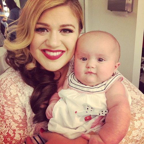 Kelly Clarkson posted this photo with her daughter River Rose on Instagram on October 6, 2014 with the caption, 'River is visiting me on the set of my new music video shoot for Wrapped In Red! #babysfirstvideo'