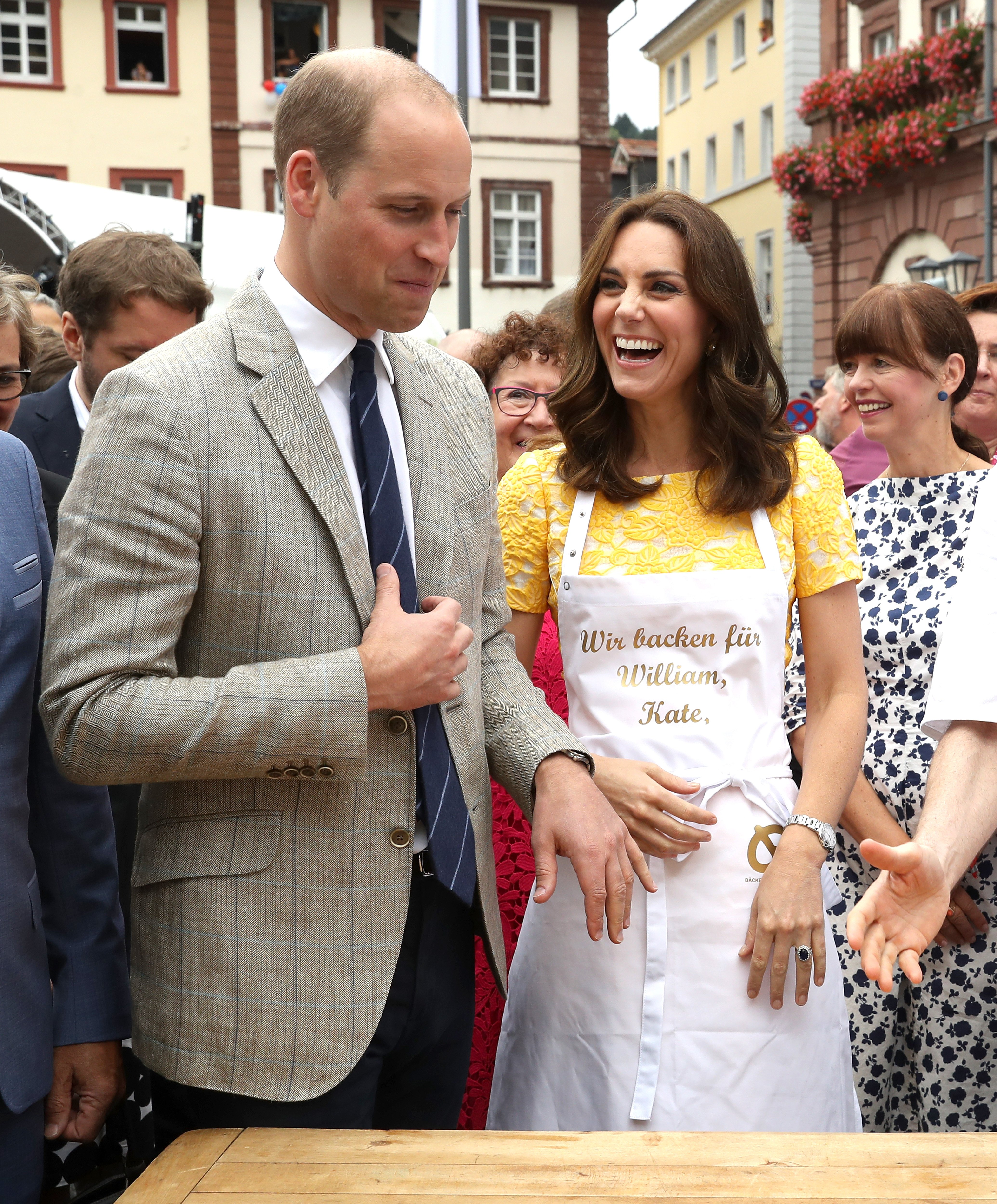 Prince William, Duke of Cambridge and Catherine, Duchess of Cambridge attempt to make pretzels during a tour of a traditional German market in the Central Square on day 2 of their official visit to Germany on July 20, 2017 in Heidelberg, Germany