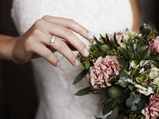 Bride wearing wedding ring near flowers