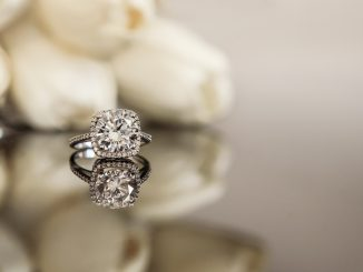 engagement ring on table with white flowers in background